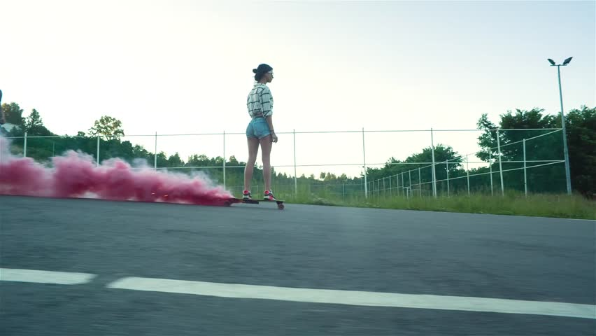 Young style woman down the road on a skateboard with red smoke in sunny summer day