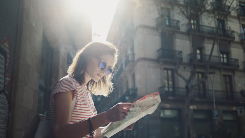 Young tourist woman exploring Barcelona map while traveling in Spain, vacation concept, flare light