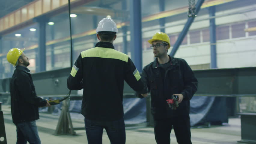 Engineer in hardhat is greeting workers with a handshake at a heavy industry factory. Shot on RED Cinema Camera.