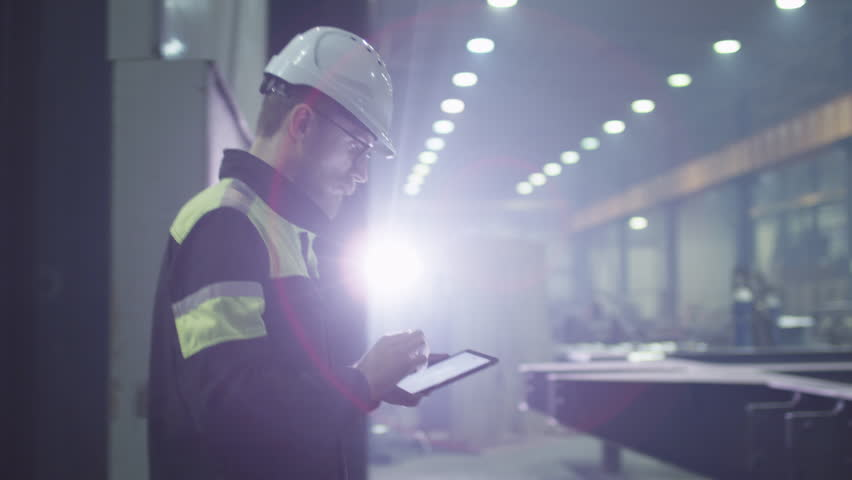 Engineer in hardhat is moving through a heavy industry factory with a tablet computer. Is greeting a worker with a handshake. Shot on RED Cinema Camera. | Shutterstock HD Video #15514921