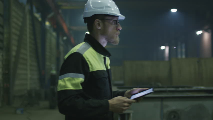 Engineer in hardhat is moving through a heavy industry factory with a tablet computer. Shot on RED Cinema Camera. | Shutterstock HD Video #15514930