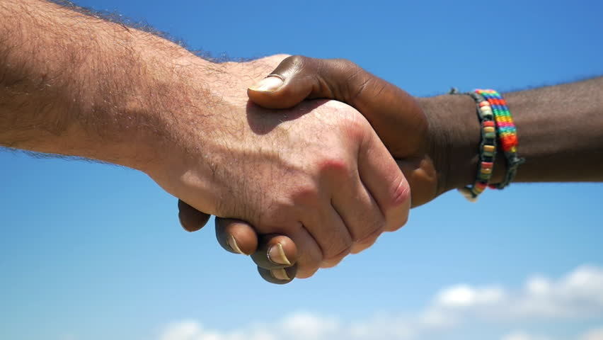 Slow motion close-up shot of European and African men shaking hands on blue sky background. International or interracial relations and friendship