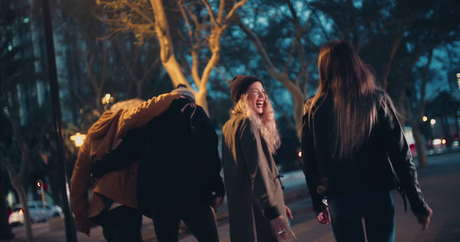 Young happy couples in winter outfits embracing while taking a night walk outside in the city | Shutterstock Video #15559708
