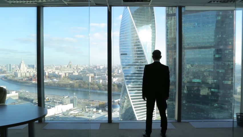 A man from a skyscraper looking over the city, silhouette, dolly,
