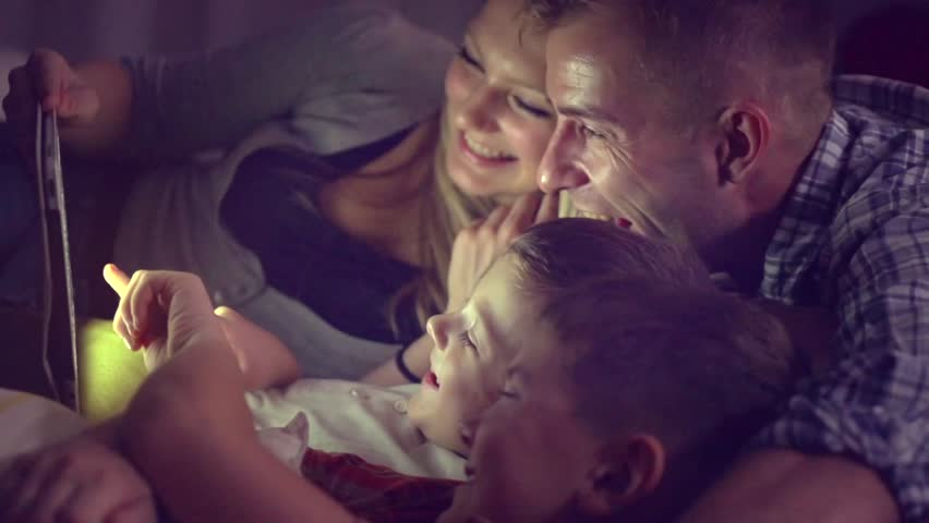 Happy family- Father, mother and Two kids lying down on the sofa and using tablet pc at night. Family watching movie on tablet computer in a dark room. HD 1080p, slow motion 240 fps, high speed camera | Shutterstock HD Video #15631360