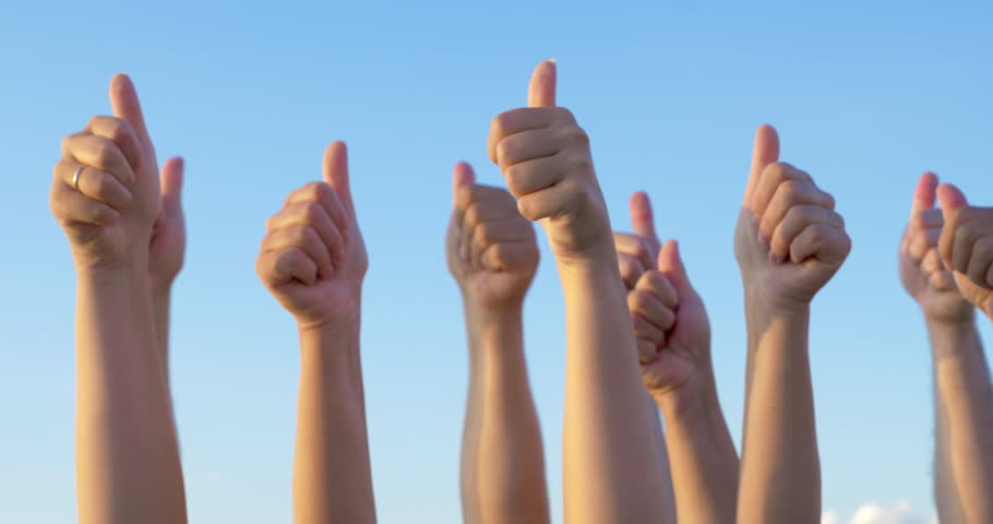 Raising hands with thumbs-up on clear blue sky background. People expressing agreement and support