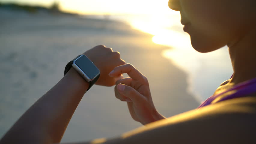 Smartwatch. Young woman using smart watch on beach. Closeup of female touching touch screen on watch entering watch app.