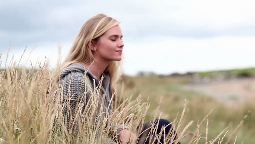 Blonde woman relaxing in the dunes in cinemagraph style