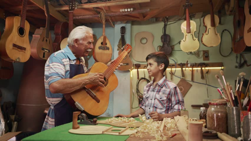 Generations and family business, old and young people showing love for music. Boy and senior man, happy kid and elderly person, grandfather teaching child how to play guitar in workshop