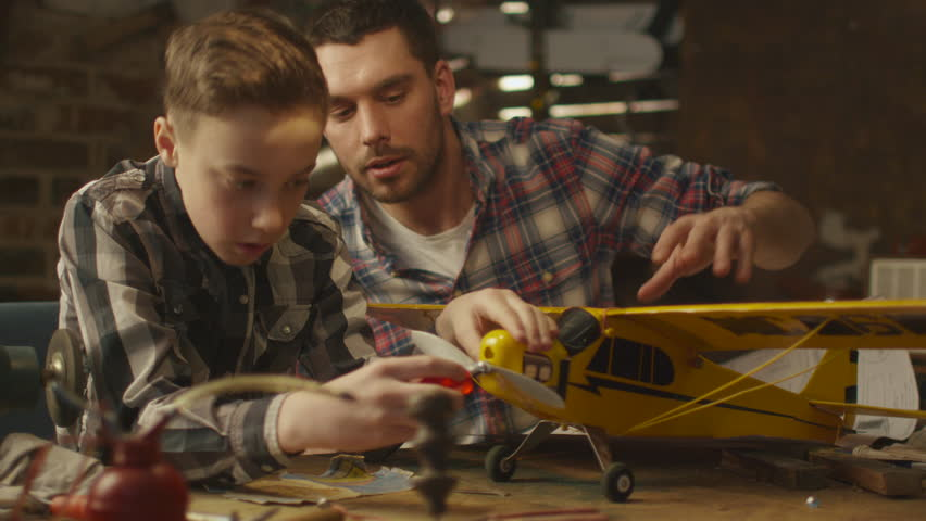 Father and son are modeling a toy airplane in a garage at home. Shot on RED Cinema Camera in 4K (UHD).
