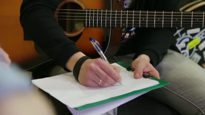 Guy with an acoustic guitar writes chords on a sheet.