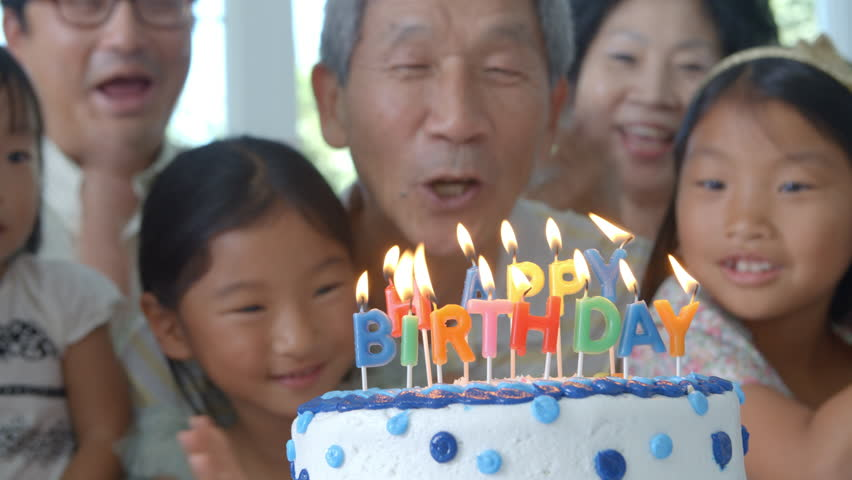 Grandfather Blows Out Candles On Birthday Cake