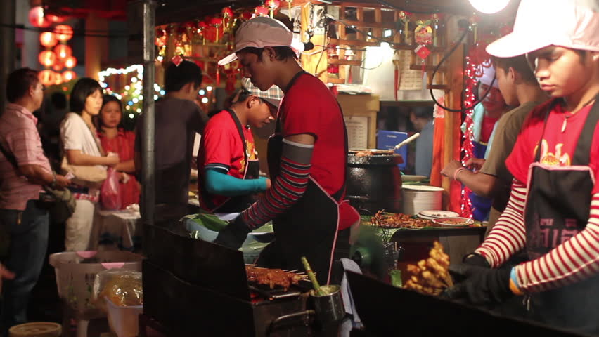CHINA TOWN, BANGKOK - FEBRUARY 11, 2013 :  During the Chinese New Year, Chinatown in Bangkok is crowded.  Young people cooking pork skewers. In evening  many restaurants are installed on sidewalks.  #16287313