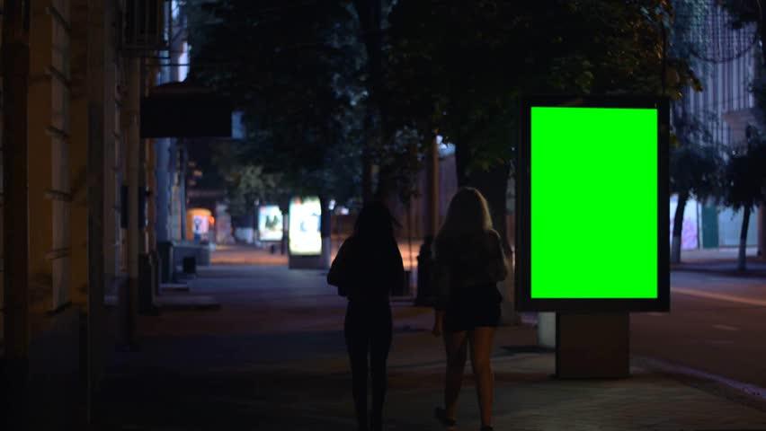 Girls walking down the street at night, Billboard template, green screen