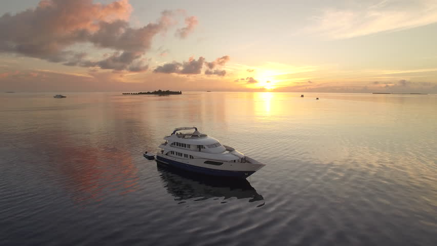 Flight over of luxury boat at tropical sunrise - Maldives Island 2015. | Shutterstock HD Video #16500961