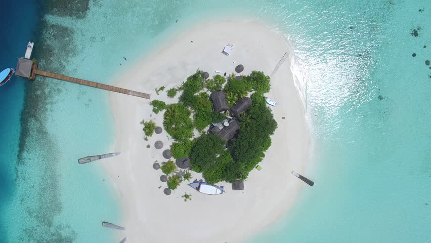 Aerial shot of a small tropical island in Maldives island, 2015. Palms and jetty on the sandbank. Camera rise up.