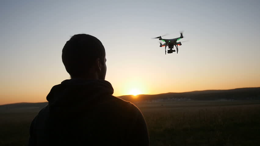 A man controls a drone at sunset #16505374