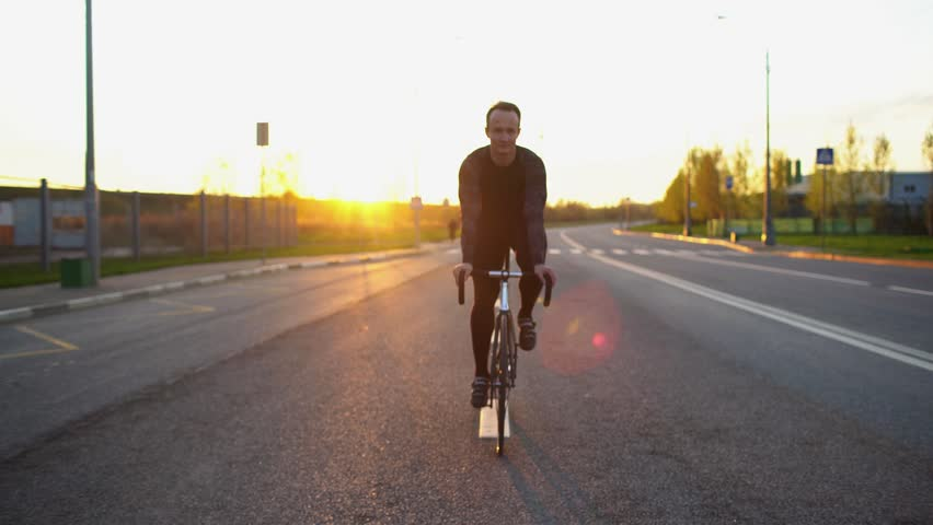 Man riding fixed gear bike on the road at sunset | Shutterstock HD Video #16703152