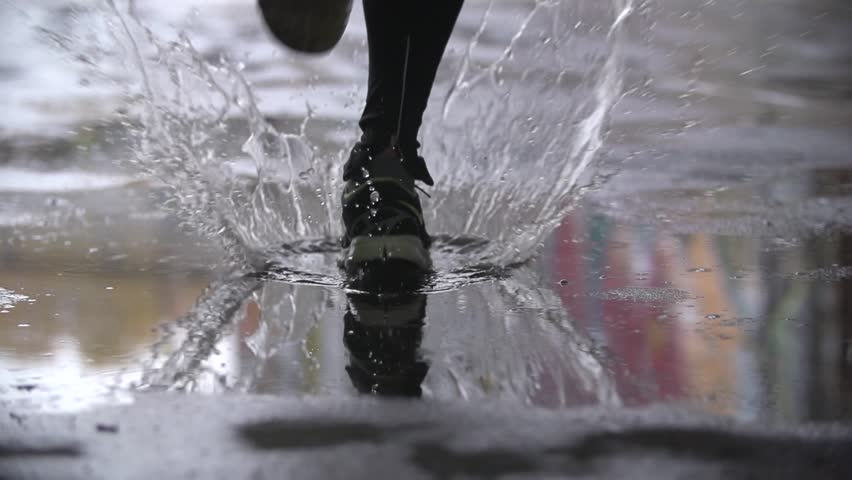Close up slow motion shot of legs of a runner in sneakers. Male sports man jogging outdoors in a park, stepping into muddy puddle. Single runner running in rain, making splash. | Shutterstock Video #16808320
