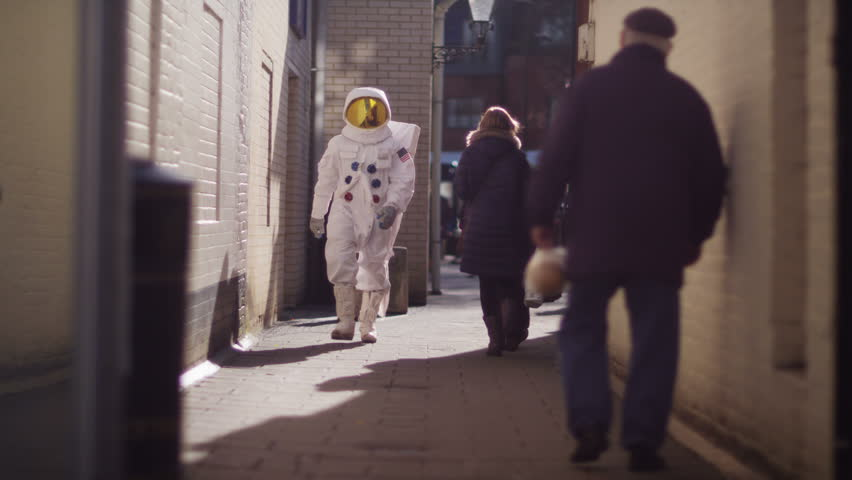 4K Funny astronaut walking through a city street...