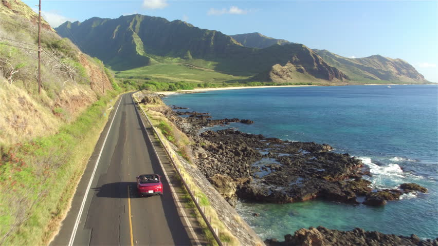 AERIAL: Red convertible car driving along the coastal road above dramatic rocky shore towards volcanic mountains. Happy young couple on summer vacation traveling at the seaside in Oahu island, Hawaii