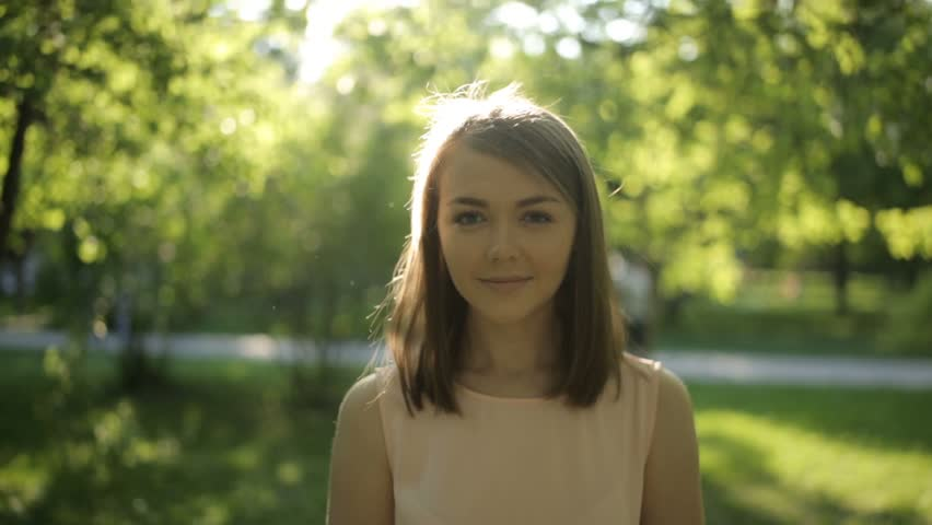 Surprisingly beautiful woman in a light blouse on background of summer park