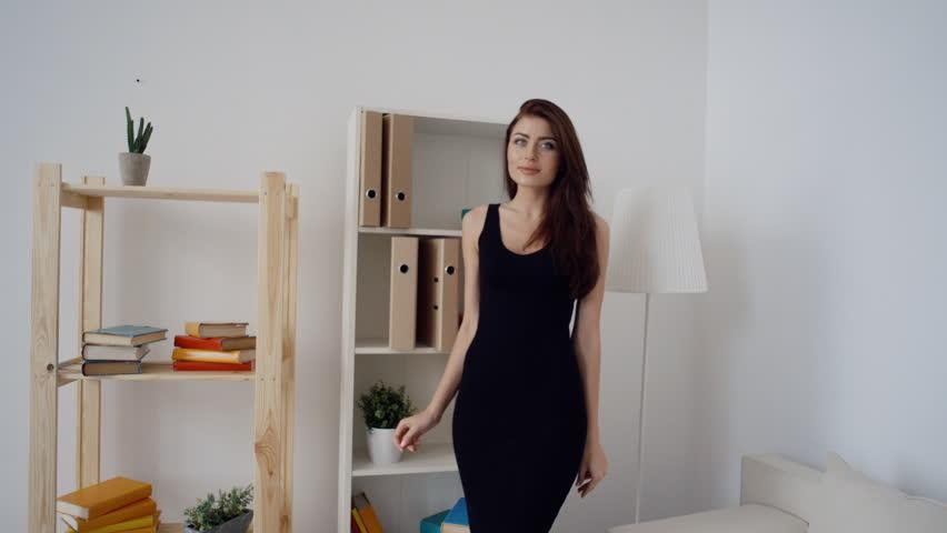 Sexy brunette business woman in fashionable black dress standing in light office | Shutterstock HD Video #17312371