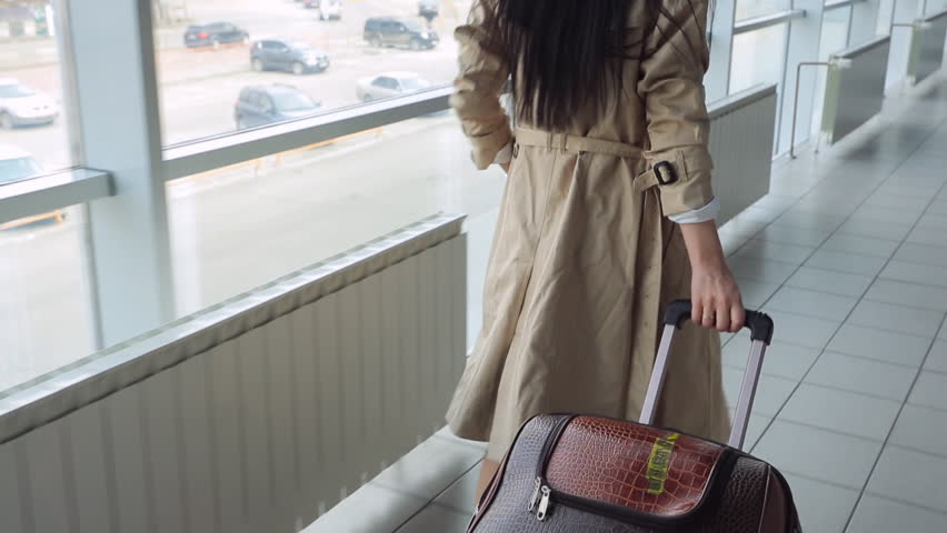 Lady in beige coat with black hair carries suitcase   Shutterstock HD Video #17442157