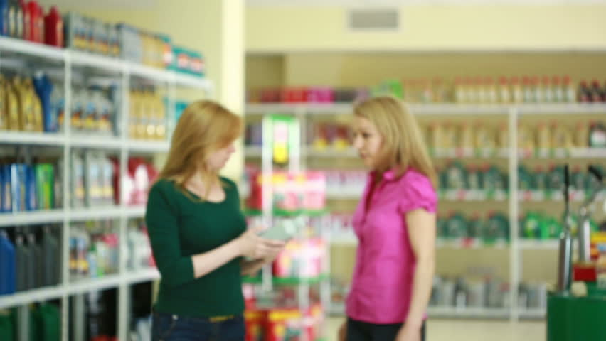 Seller in the store helps girl to choose engine oil.   Shutterstock HD Video #17482576