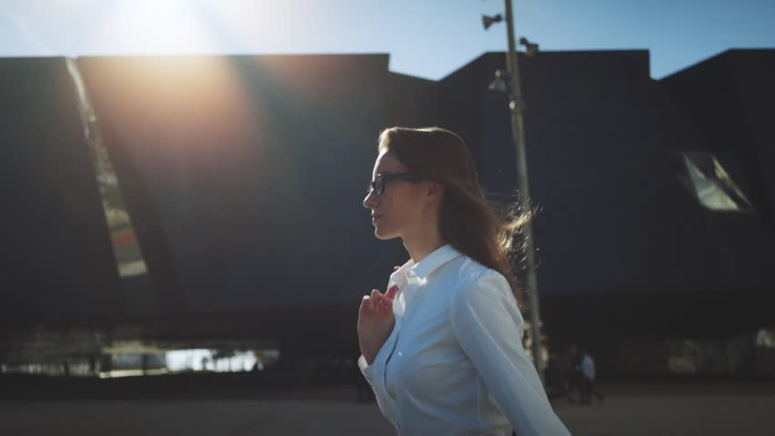 Side view of young successful businesswoman wearing modern suit and walking in the city at break, flare light, sunshine,  slow motion | Shutterstock HD Video #17524660