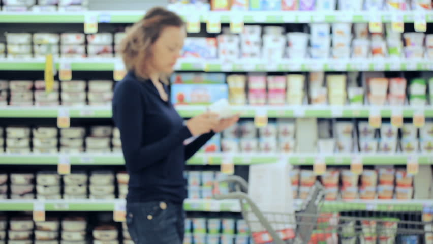 Young woman shopping in the yogurt section at the grocery store.   Shutterstock HD Video #17725921