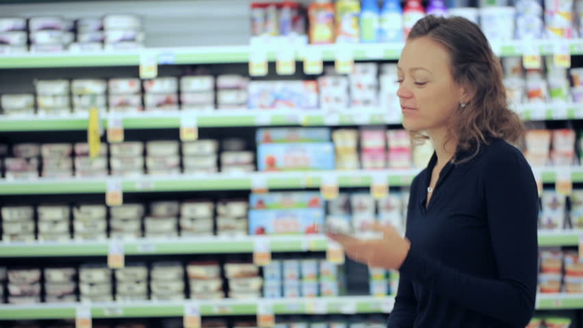 Young woman shopping in the yogurt section at the grocery store.   Shutterstock HD Video #17725933