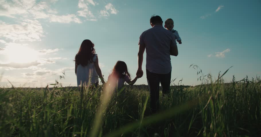 young happy Asian family goes on a green field with two children, slow motion