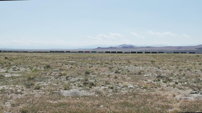 GREAT BASIN DESERT, WESTERN UTAH - JUNE 2016: POV-Side window driving view of a far distant train running parallel to road in a vast empty desert.   Shutterstock HD Video #17763142