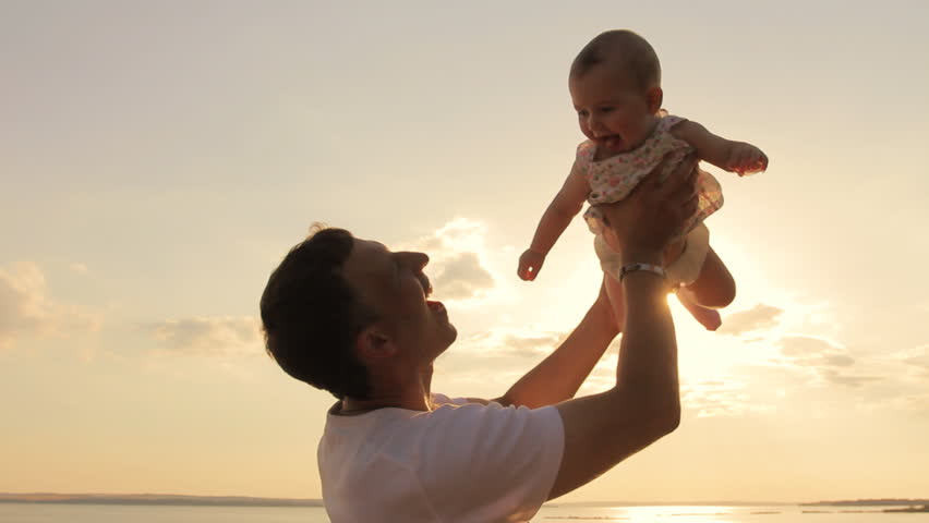 Happy man playing lifting his daughter outdoors. Silhouette of young father holding up his cute baby daughter in air against sunset sky playfully