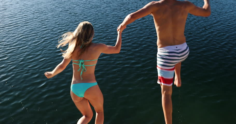 Young Adult Couple Holding Hands Jumping Into Lake