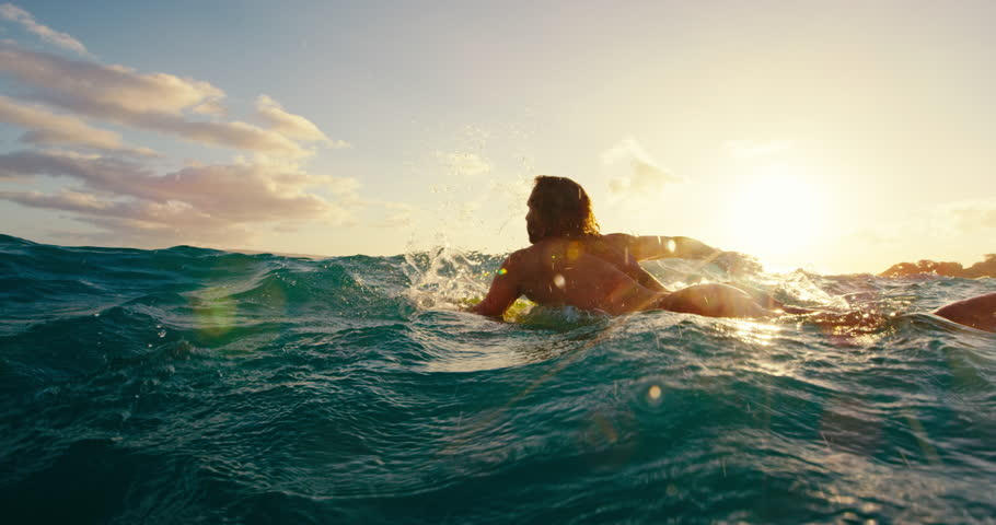 Surfer paddling over blue ocean wave at sunset in slow motion, outdoor fitness lifestyle