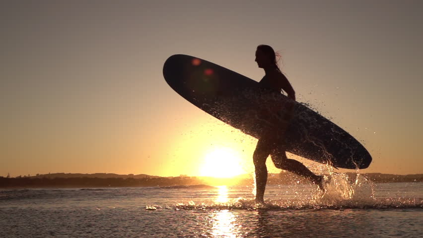 SLOW MOTION SILHOUETTE: Young surfer girl enjoying seaside summer vacation activities, holding longboard surfboard and running in shallow water in beautiful ocean at amazing golden light sunset | Shutterstock Video #18000454
