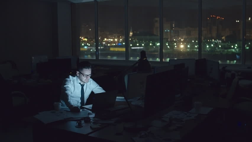 Tired sleepy man sitting at desk in dark office at night and working on laptop, drinking coffee and trying to concentrate, wide shot on Sony NEX700 + Odyssey 7Q | Shutterstock Video #18171358
