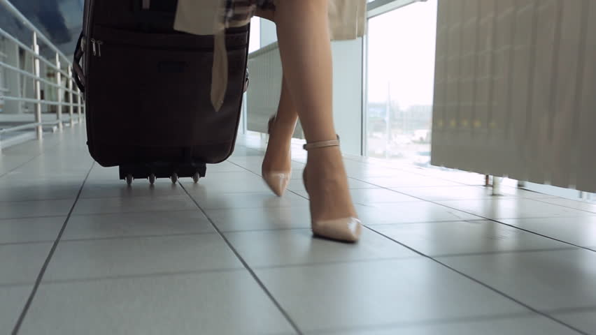Woman in heels goes at airport and roll suitcase on wheels.   Shutterstock HD Video #18278554