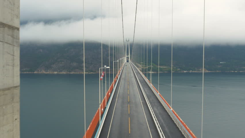 Aerial Shot Car Crossing Suspension Bridge across River in Norway. Weather is Foggy and Cloudy.
