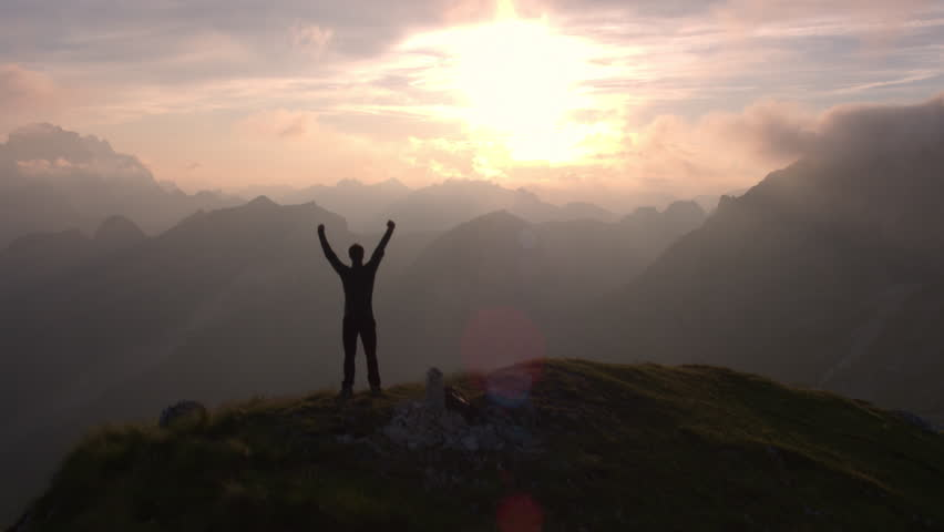 Aerial - Flyover silhouette of a man standing on top of the mountain. Man raising arms victoriously after climbing the mountain