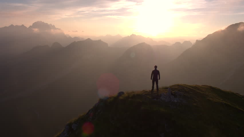 Aerial - Flyover silhouette of a man standing on top of the mountain and watching beautiful sunset over the peaks