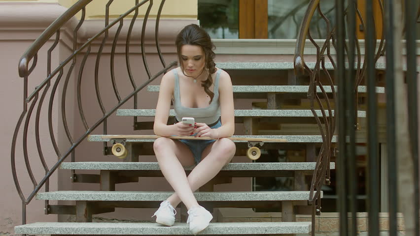 4K CINEMAGRAPH - motion photo seamless loop - Hipster girl sitting on the stairs with a longboard skateboard and listening to music on the phone through earphones. 60 FPS 4K UHD | Shutterstock Video #18432856