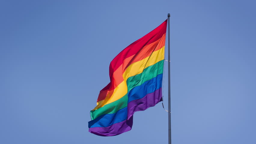 Gay pride flag blowing in the wind on Sitges