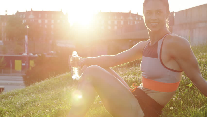 Athletic young woman taking a break from her exercise workout to drink a bottle of water sitting on a grassy urban embankment with bright sun flare | Shutterstock HD Video #18566774