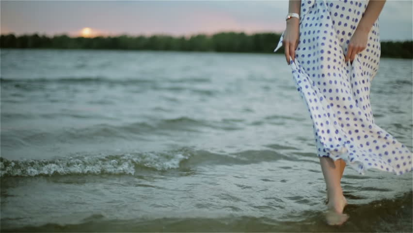 Woman's bare feet in the water of the lake. The girl enjoying the warm waters at sunset. Wind is ruffling white polka-dot dress. Long skirt is waving on a wind. Slow motion.