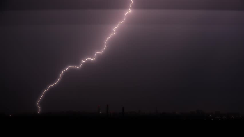 Lightning flashes over a city during a strong thunderstorm.