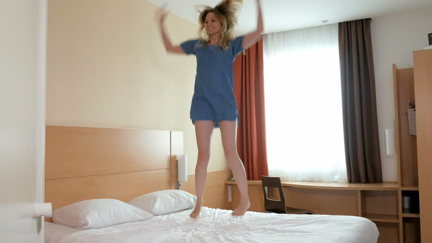 cheerful young slim blonde dressed in blue dress is jumping on snow white  bed in. Dancing In Bedroom