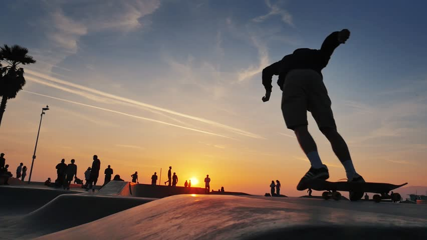 Silhouette of skater on skateboard jumping over sunset sky at Venice Beach skate park, California. Slow motion. | Shutterstock Video #18784256